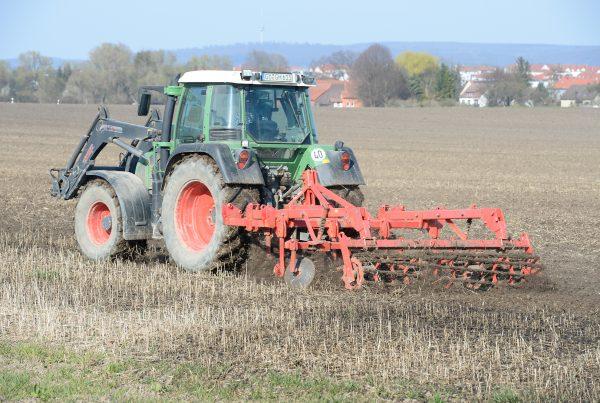 Traktor der über ein Feld fährt und düngt